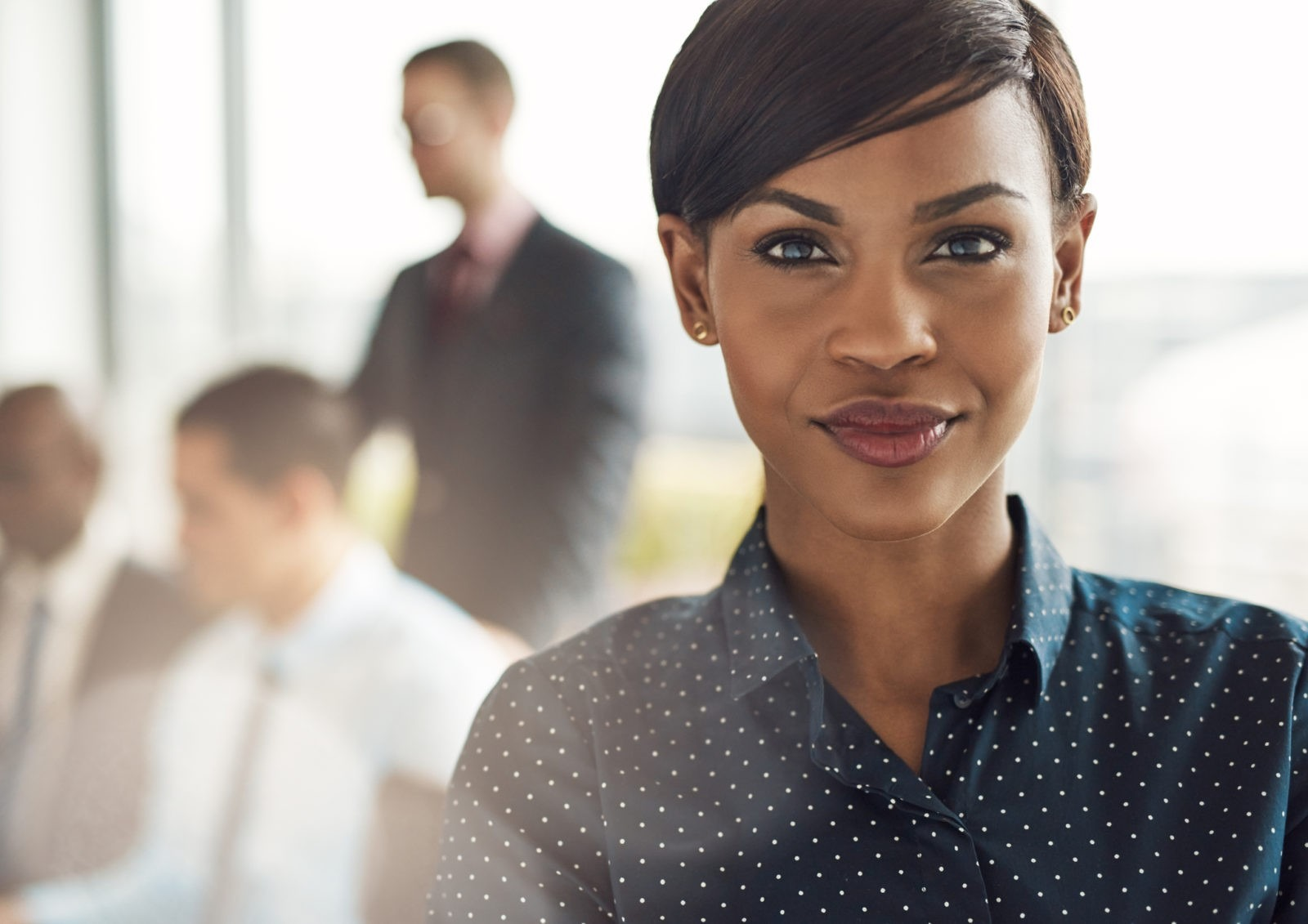 Confident business woman in office with group
